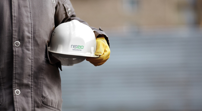 A worker holding a nexeo solutions hard hat